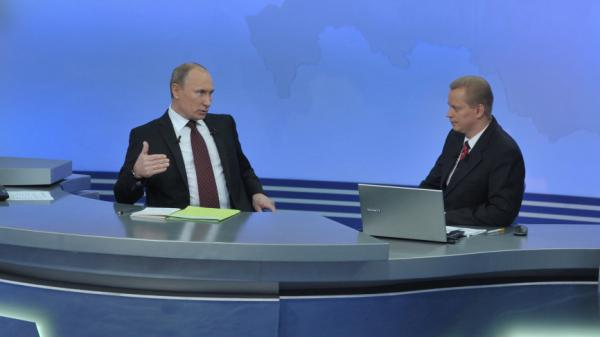 Russia's Prime Minister Vladimir Putin (L) speaks during a phone-in TV program in Moscow on Thursday. With widespread fraud alleged in recent parliamentary voting, Putin faced much more critical questioning than usual.