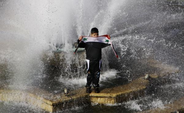 A boy stands in a water fountain as he holds up the Syrian national flag during a rally in Damascus, Syria.