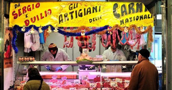 A butcher shop serves customers in a Rome market on Dec. 31. A new law went into effect in Italy on Jan. 1, allowing shops, cafes and restaurants to stay open 24/7 throughout the year.
