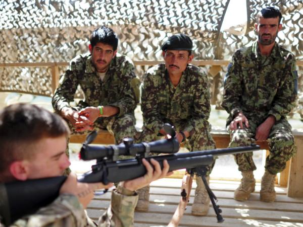A U.S. soldier with a sniper rifle provides instruction to Afghan troops in the eastern province of Paktika last September.