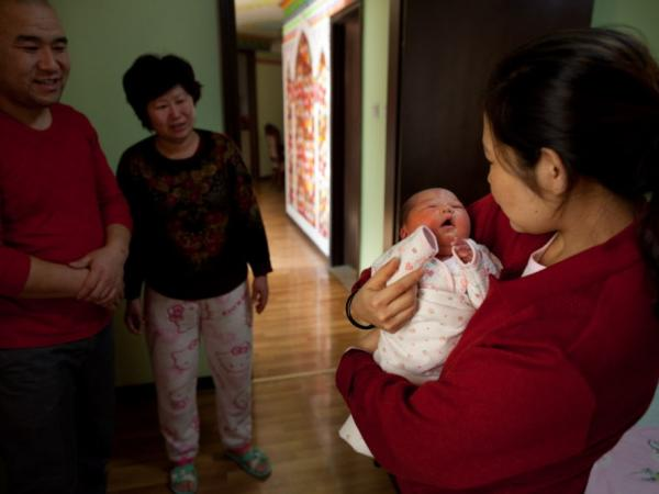 Yu Qiuyan (right) held her newborn baby girl Li Muhua, as father Li Wanhong (left) and a relative stood by in Beijing on January 26.