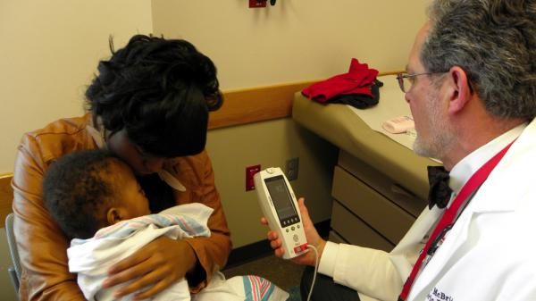 Dr. John McBride examines 9-month-old Martez after his mother, Ceasha Moorer, brought him in to check on his asthma.