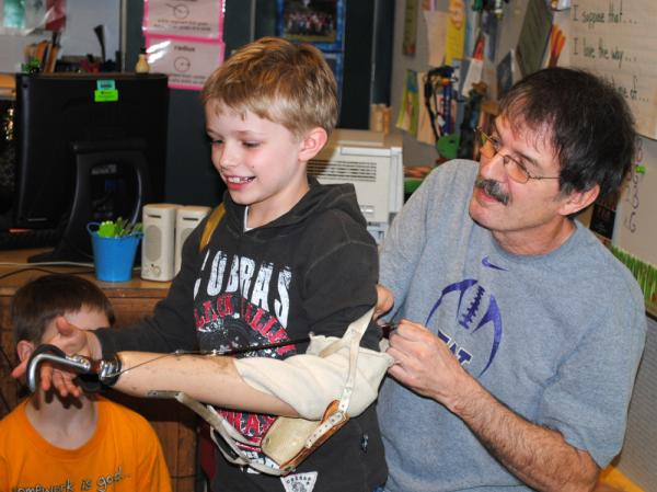 Ron Cushman's 8-year-old grandson, Shaun, tries out his grandfather's prosthetic arm. Cushman would let his students try out the arm on the first day of school.