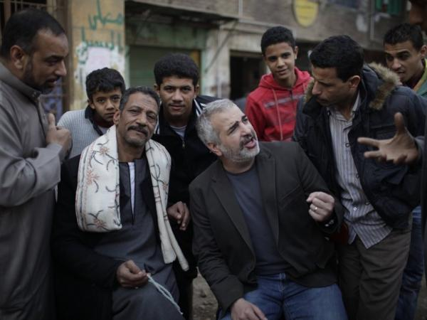 <em>New York Times</em> journalist Anthony Shadid often wrote about ordinary citizens caught up in war zones. Shadid (center), who died last week in Syria, is shown here talking to Egyptians in Cairo during the revolution that toppled then-President Hosni Mubarak in February 2011.