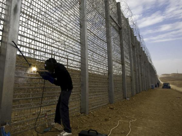 A worker builds part of Israel's border fence near the Red Sea resort town of Eilat in February. Many illegal immigrants to Israel slip across the country's border with Egypt.