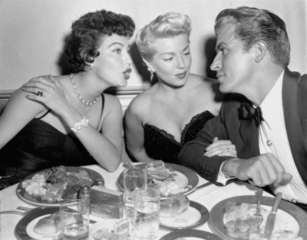 "Lana Turner, center, is an interested listener as actress Ava Gardner leans over her to chat with Fernando Lamas, who is famous for saying, ""It's better to look good, than feel good."""