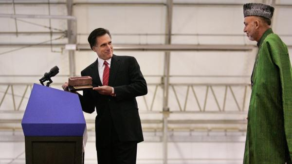 In this 2005 photo, then-Massachusetts Gov. Mitt Romney presents Afghan President Hamid Karzai with a memento at Boston's Logan Airport. Karzai was preparing to speak at Boston University's commencement.