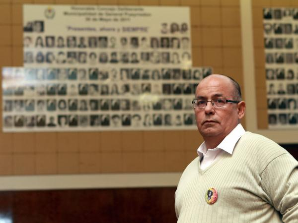Human rights activist Carlos Diaz stands in Mar del Plata City Hall, where a wall displays portraits of the victims of a 1970s-era military dictatorship in Argentina.