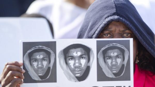 At a rally in Miami on Sunday, Arleen Poitier held a sign with images of Trayvon Martin.