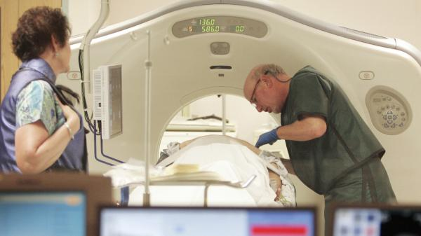 Dr. Steven Birnbaum positions a patient inside a CT scanner at Southern New Hampshire Medical Center in Nashua, N.H., in June 2010.