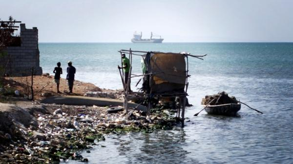 A makeshift latrine hangs over the water at the edge of Cite de Dieu, a slum in Port-au-Prince, Haiti.