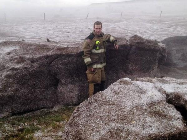 This photo provided by the Amarillo/Potter/Randall Office of Emergency Management shows Potter County firefighter Matt Dryden standing next to a wall of hail on Wednesday near Amarillo, Texas. The hail was pushed into drifts of up to 4-feet.