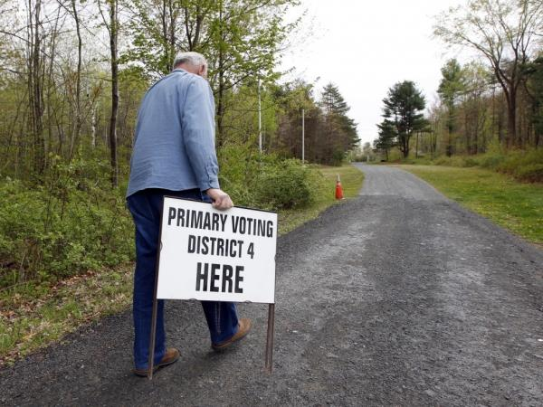 A man prepares to put in place an informational sign for voters on primary day 2012 in North Greenbush, N.Y.