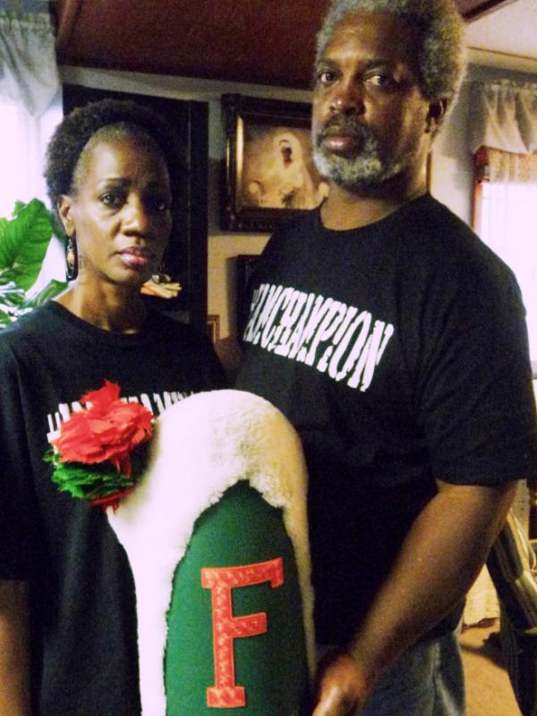 Pam and Robert Champion hold their son's drum major hat from Florida Agricultural and Mechanical University. Robert Champion Jr. died after a hazing incident in November.