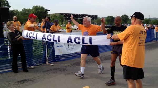 Sen. Dick Lugar, R-Ind., crosses the finish line of the 3-mile Capital Challenge charity race with Olympic marathoner Meb Keflezighi. It was Lugar's 31st race, and his last as a senator after he lost a primary challenge this month.