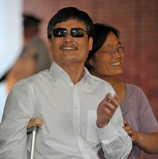 Chinese activist Chen Guangcheng and his wife Yuan Weijing arrive at the New York University Village apartment complex in New York Saturday.