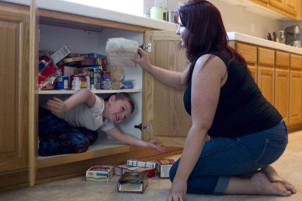 Jaden climbs into a kitchen cabinet, removing the food from the shelves so he can fit. Amber says she can't afford to buy him new shoes or clothes because of her health care expenses.
