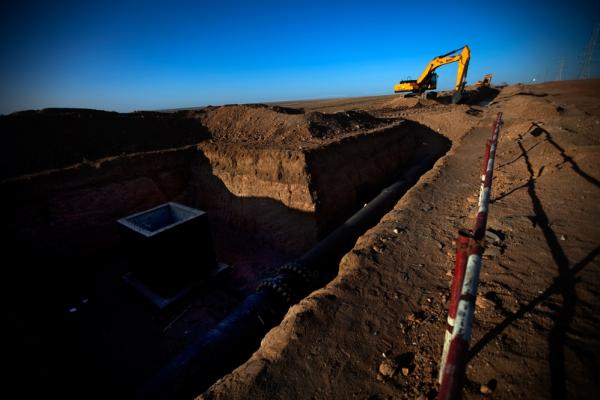 "A construction crew works on a section of an underground water pipe and wellhead the Oyu Tolgoi mine is building along the dirt ""highway"" in South Gobi."