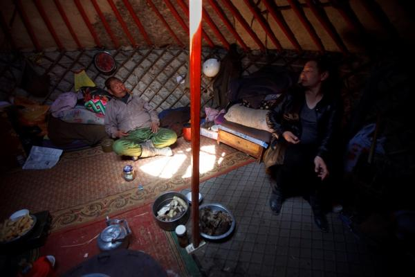 In South Gobi province, a local politician (right) and a herder sit inside a traditional yurt, or <i>ger</i>, and discuss the lack of water in the area. Herdsmen worry that mines — which require massive amounts of water to process ore — will deplete already diminishing supplies.