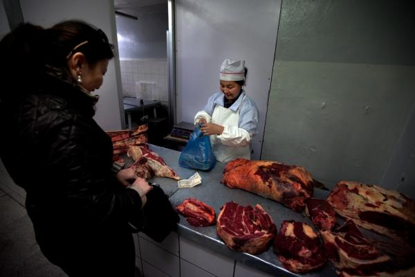 Mutton is a staple of the Mongolian diet. A woman buys meat from a butcher in Ulan Bator's central market.
