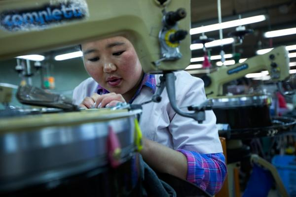 A seamstress performs delicate work on a piece of cashmere cloth at the Gobi factory. The cashmere industry is also feeling the effects of mining — as inflation has driven up the cost of raw materials, and water shortages and shrinking pastureland threaten herds.
