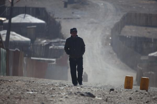 A <i>ger</i> district resident walks the dusty streets on the outskirts of Ulan Bator. As Mongolia's mining industry continues to grow, the future of the country's traditional ways is unclear.