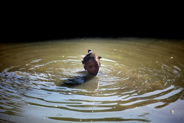 A young girl cools off from the midday heat in an irrigation canal near Saint-Marc. People in this area were chosen for the pilot vaccination program because they draw their water from the contaminated Artibonite River.