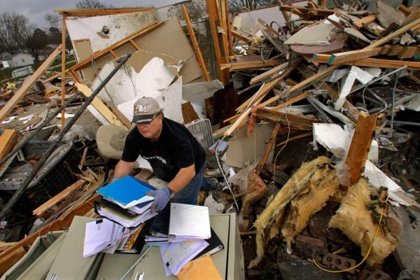 Joe Jenkins helps salvage medical records from a destroyed senior center in Harrisburg, Ill.