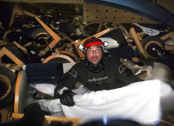 A scuba diver makes his way through floating pieces of furniture while searching for people inside the cruise ship.