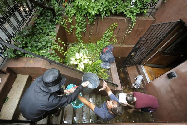 People form a bucket brigade to bail water out of a flooded Chelsea apartment in New York on Sunday.