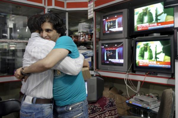 Afghan men hug each other while watching the news of bin Laden's death. Bin Laden was killed in a firefight with U.S. forces at a compound in Abbottabad, Pakistan, early Monday.