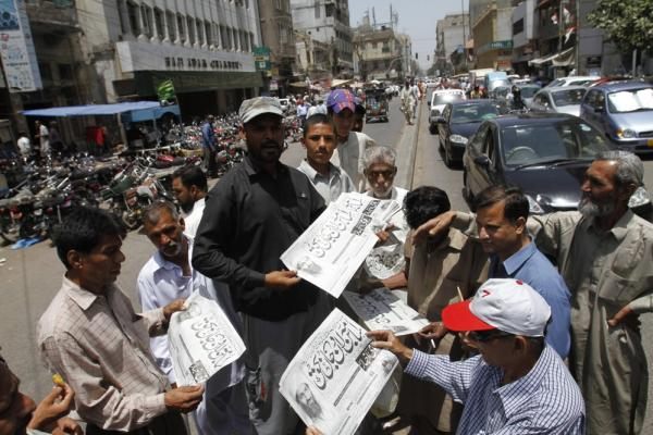 Men in Karachi, Pakistan, buy newspapers reporting the killing of bin Laden.