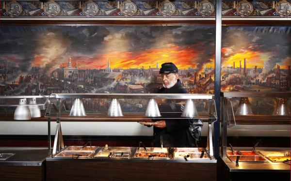 Ben Hawley, 54th Massachusetts, at Pickett's Buffet, Gettysburg, Pa. The 54th Massachusetts infantry, a unit of black Union soldiers, was portrayed in the film <em>Glory</em>. The mural behind Hawley depicts the collapse of the Confederacy.