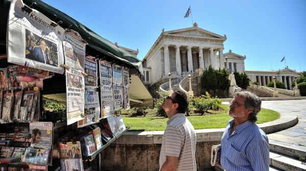 Two men read newspaper headlines in Athens on Monday as conservative Greek lawmakers raced to form a government a day after parliamentary elections.