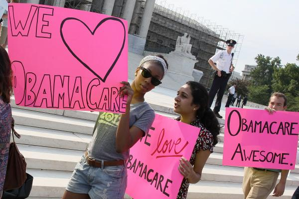 Supporters of the health care law march in front of the Supreme Court building.