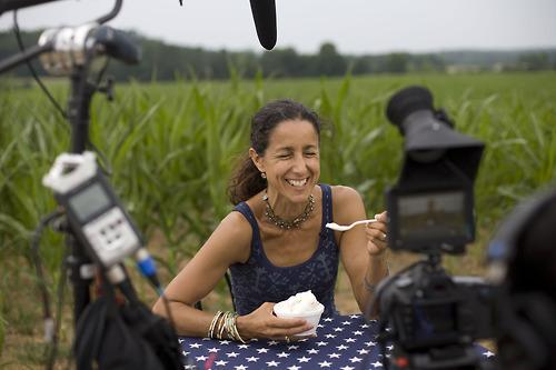 "Filmmaker Julie Winokur sits at ""The Table"" at Maple View Farm in Hillsborough, N.C. She is traveling the country with a folding table and a star-spangled tablecloth, asking people to share their political beliefs."