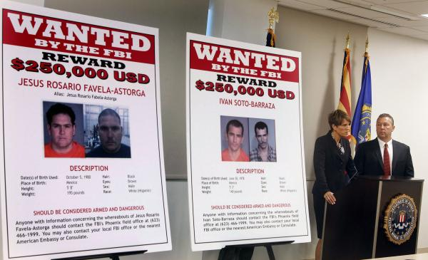 With wanted posters off to the side, James L. Turgal, Jr., right, FBI Special Agent in Charge, listens as Laura E. Duffy, United States Attorney Southern District of California, announces the indictments on five suspects involved in the death of U.S. Border Patrol agent Brian Terry on Monday.