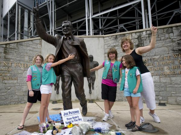A Pennsylvania Girl Scout Troop poses with the statue of former Penn State University football coach Joe Paterno outside Beaver Stadium in State College, Pa., on Saturday.