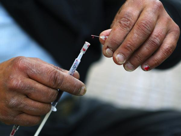 Vicky, a 40-year-old, Canadian-born, Greek drug addict, takes a drop of her own blood from a syringe as she prepares to inject herself with a mix of cocaine and heroin on a central Athens side street, April 30.