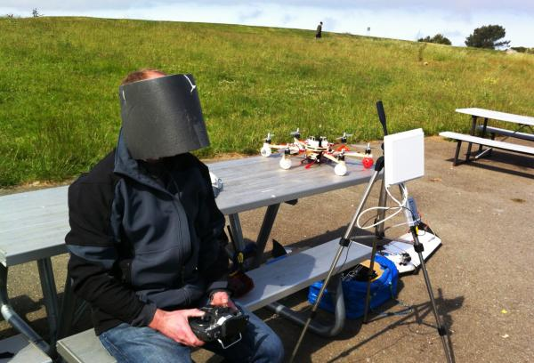 Drone enthusiast Andreas Oesterer wears homemade video goggles, wrapped in gray foam to block out the glare of the sun, as he flies a drone over Cesar Chavez Park.