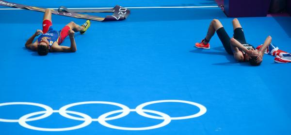 Triathlon gold medalist Alistair Brownlee of Britain (right) and silver medalist Javier Gomez of Spain lie on the ground after crossing the finish line in the London Games.