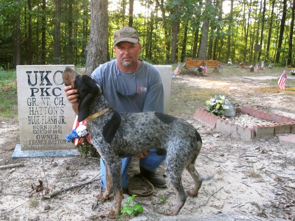 Franky Hatton and Cletis pose in front of the gravestones of Hatton's champion coon hounds at Coon Dog Cemetery.