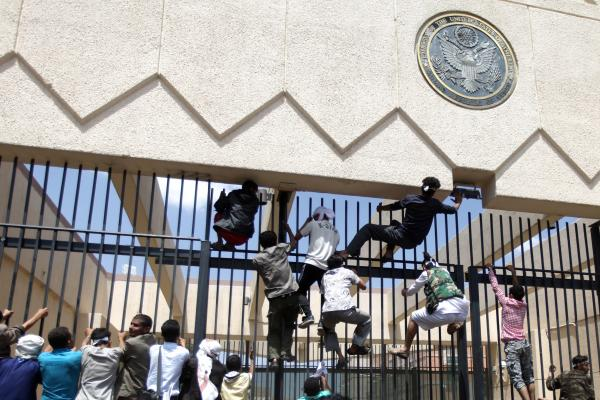 Protesters climb a fence at the embassy as security guards fire warning shots into the air.