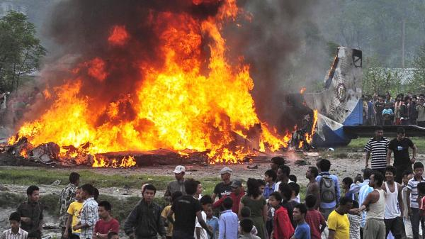 Plane wreckage burns near the airport in Katmandu, Nepal, following an accident that killed 19 people aboard.