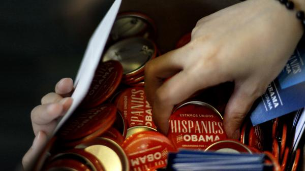 A volunteer hands out buttons before first lady Michelle Obama speaks at a Hispanic caucus on Sept. 5 in Charlotte, N.C.