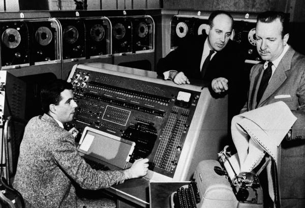 Walter Cronkite (right) listens as Dr. J. Presper Eckert (center) describes the functions of the UNIVAC I computer he helped develop in the early 1950s.