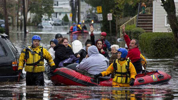 First responders rescue flood-stranded people in Little Ferry, N.J., on Tuesday.