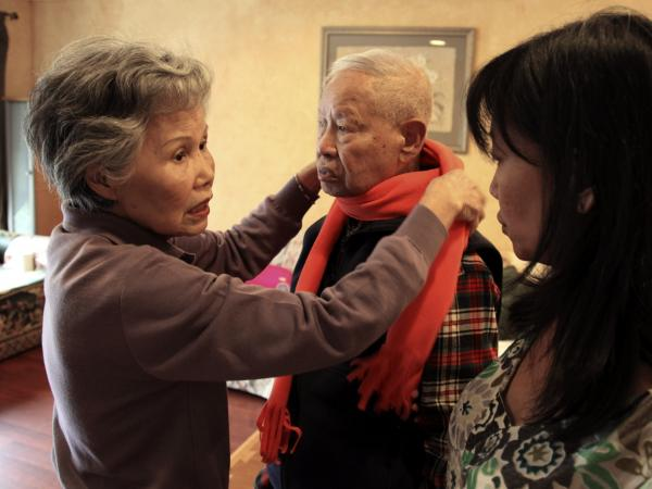 Shou-Mei Li, left, wraps a scarf around her husband Hsien-Wen Li, who is an Alzheimer's patient, as their daughter Shirley Rexrode, right, looks on, at their home in San Francisco.