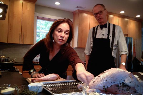 <em>Morning Edition</em>'s RenŽee Montagne reaches for the prepared turkey as Kimball explains how Child's recipe calls for the turkey breast to be butterflied and separated from the thighs and legs and cooked in different pans.