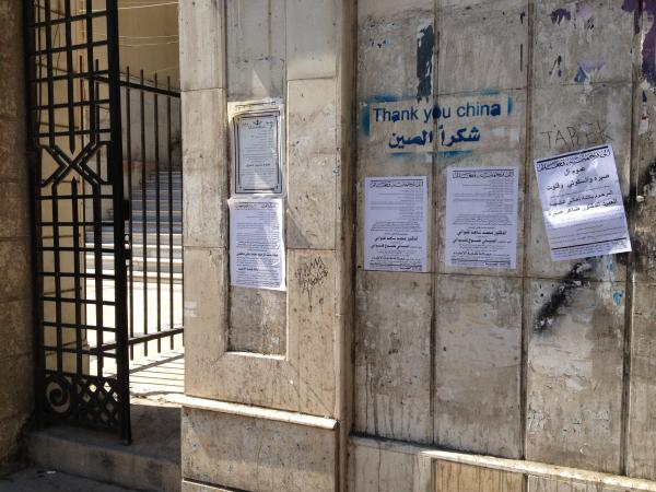 Death notices hang on a wall alongside pro-regime graffiti in central Damascus.